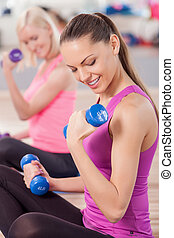 Cheerful fit girls are doing exercise with weights -...