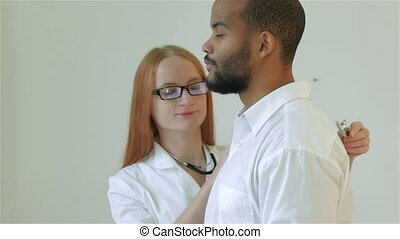 Nice doctor listens to the patient stethoscope
