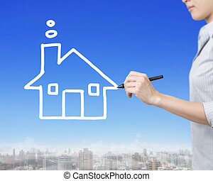 Woman hand holding pen drawing house shape clouds in sky