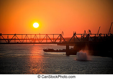 Evening sunset near the railway bridge and big fountain in...