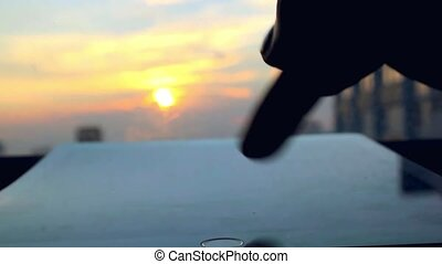 Women hands using tablet on the blurred sunset sky and...