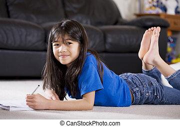 Little girl doing her homework lying on floor