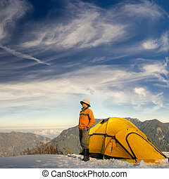 Man stand with yellow tent on snow hill against dramatic...