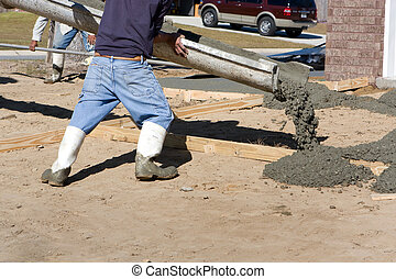Pouring Concrete Driveway - Construction worker directs a...