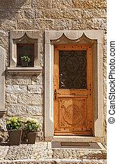 Vintage wood medieval door in rural stone wall house, Switzerland