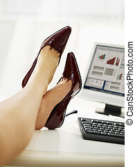 businesswoman with feet on table taking off shoes - business...