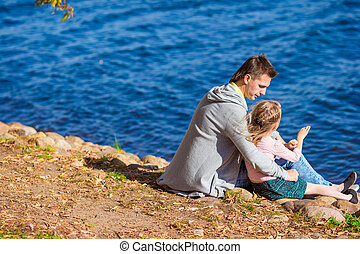 Little adorable girl with happy father near river at warm autumn day