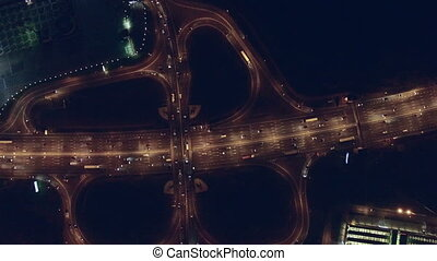 Aerial vertical view at night of city traffic on large...