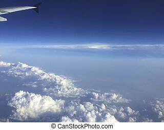 Aircraft Wing above Clouds - Ailerons and flaps tucked flat...