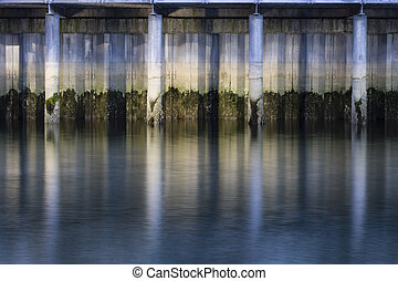 Under the Bridge - smooth water and pillars under a...