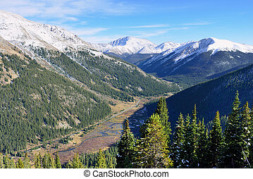 overlook of the snow covered mountains, trees and mountain creek from above