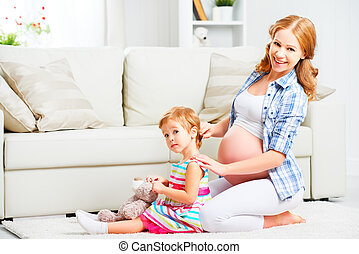 Happy family pregnant mother combing hair of little daughter...