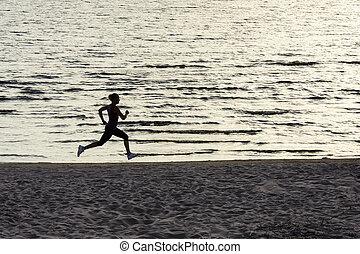 Young woman running along lake shore at sunset