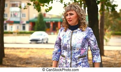 full fat middle-aged woman on phone in the park behind the cars drive lifestyle