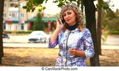 full woman fat middle-aged on phone in the park behind the cars drive lifestyle