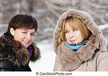 Two young women in frosty day outdoors closeup photo