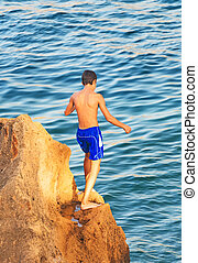 Boy getting ready to jump into the water.