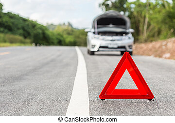 Red emergency stop sign and broken silver car on the road
