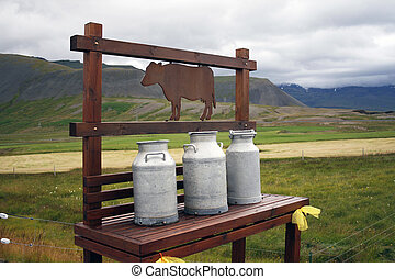 Milk churns in rural landscape