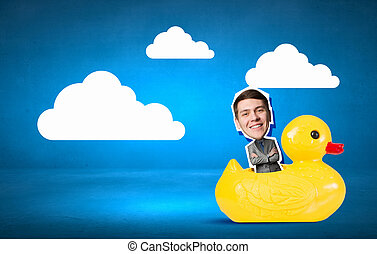 Businessman on rubber duck - Young happy businessman riding...