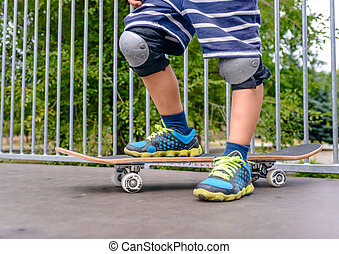 Young boy standing at the top of a ramp