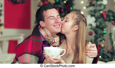 Young beautiful couple holding hands with a cup of cocoa -...