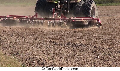 Tractor plowing field with dust rising on sunny dry day
