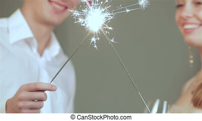 Beautiful couple in Santa hat with sparklers in their hands together