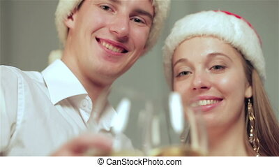Beautiful couple at Christmas with glasses of champagne looking at camera