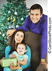 Family with Christmas present near the Christmas tree -...