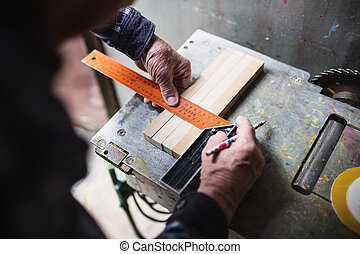 Old carpenter taking measurement of a wooden plank