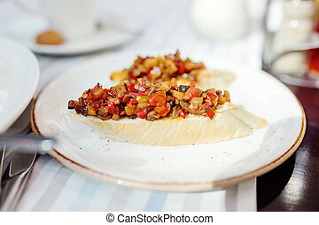 Bruschette, traditional italian appetizer food with tomato and eggplant on plate.