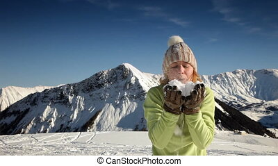 woman blowing on snow - young woman blowing on snow in Le...