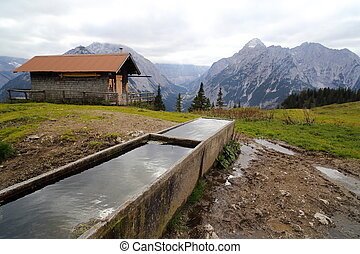 watering place with hut and mountains in background