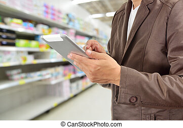Young Man Hands holding Tablet in Supermarket - Young Man...