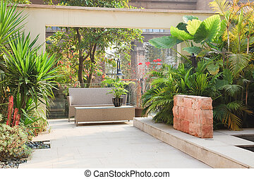 Backyard Patio in Garden - Backyard with cane chair and tree...