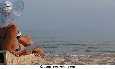 Tanned woman reading a book on the beach.