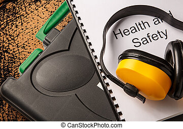 Black toolbox with earphones and health and safety document