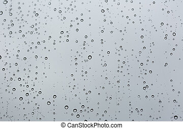 Cold rain drops on window as background