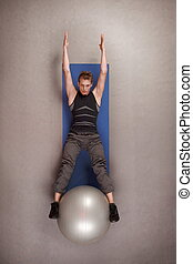 man practicing pilates on ball - Overhead view of man...
