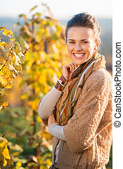 Smiling woman winegrower standing in vineyard outdoors in...