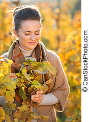 Relaxed woman winegrower standing among grape vines in...