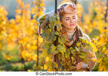 Relaxed woman winegrower standing in vineyard outdoors in...