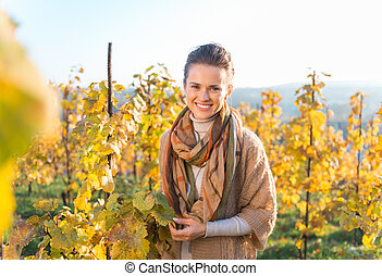 Smiling young woman winegrower standing in autumn grape...