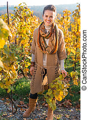 Portrait of woman winegrower standing in autumn grape field...