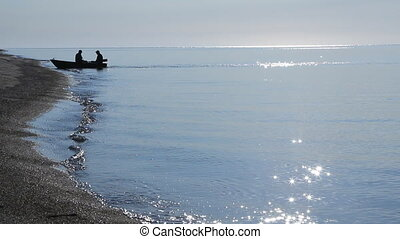 The boat with the fishermen moor to the shore