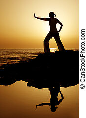 Sunset Yoga with Reflection - Yoga woman silhouetted against...