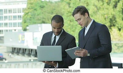 Two businessman holding a tablet and laptop in hand -...