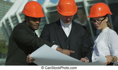 Three confident business architect in protective helmet...