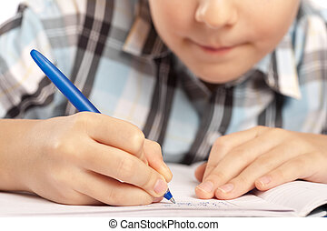 Anonymous kid doing homework - Close up of a schoolboy doing...